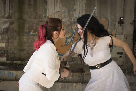 two young women dueling with swords
