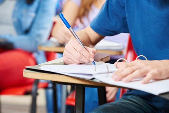 teen taking notes in class