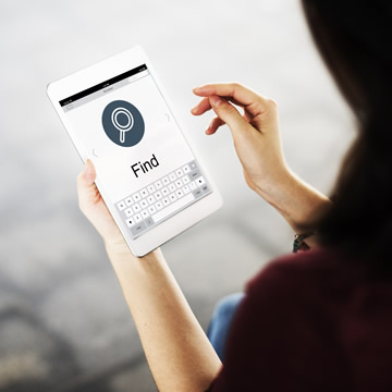 woman holding a tablet with a search screen displayed