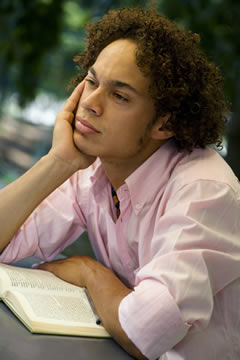 teen thinking while reading a book