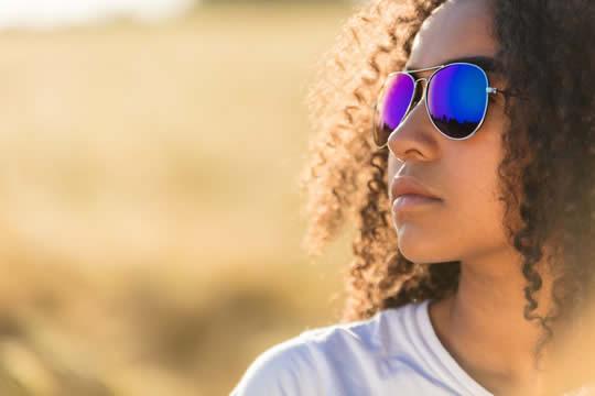 teen thinking, wearing reflective sunglasses