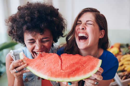 girls laughing and eating watermelon