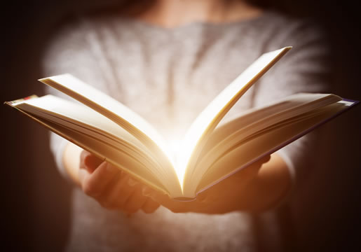 someone holding an open book that is glowing