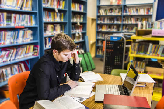 teen boy reading books in the library
