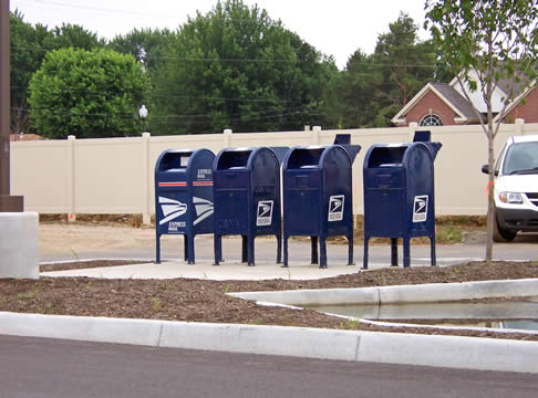 four United States Postal Service mailboxes in a parking lot