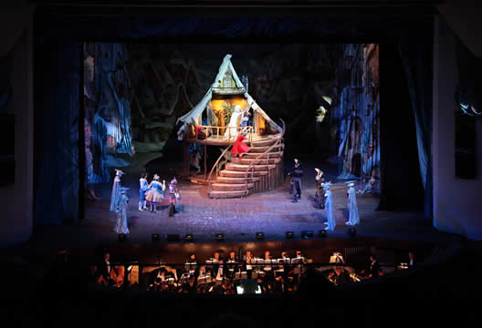 a theatrical performance showing stage, performers, and orchestra