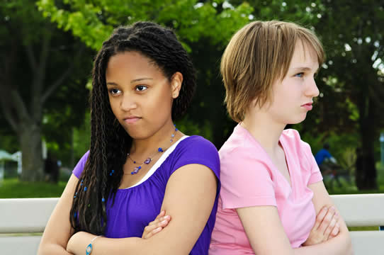 two angry teenage girls with their backs to each other and arms crossed