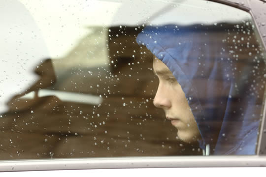 teenage boy looking out car window with raindrops