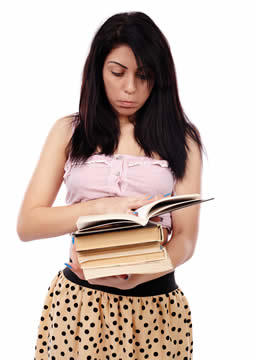 student holding a pile of books and reading the top one