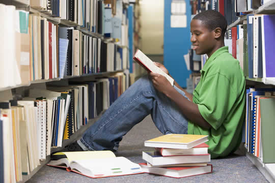 African American student sitting on floor in library, reading