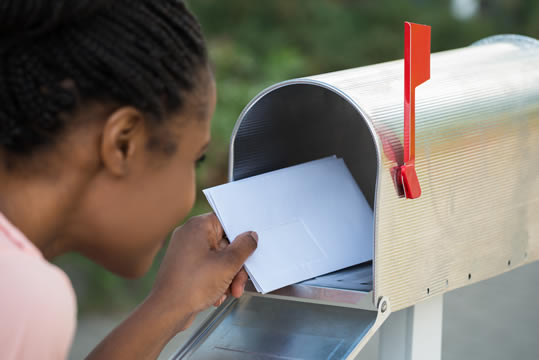 young woman taking letters from mailbox