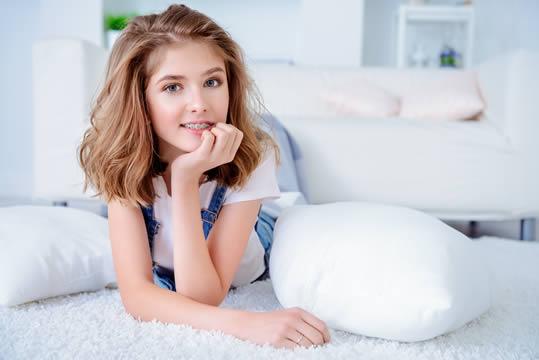 teenage girl with braces lying on bed