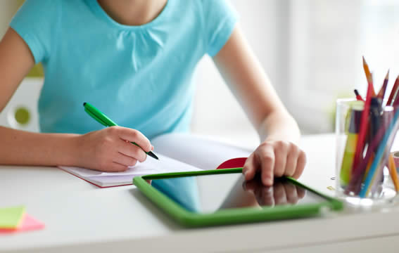 girl writing a letter and checking something on a tablet on the desk