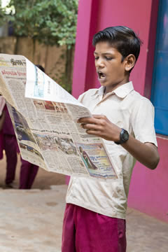 boy reading a newspaper, showing surprise on his face