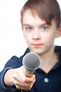 boy holding microphone to conduct an interview