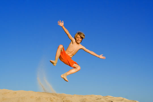 boy in bathing suit jumping in sand dune