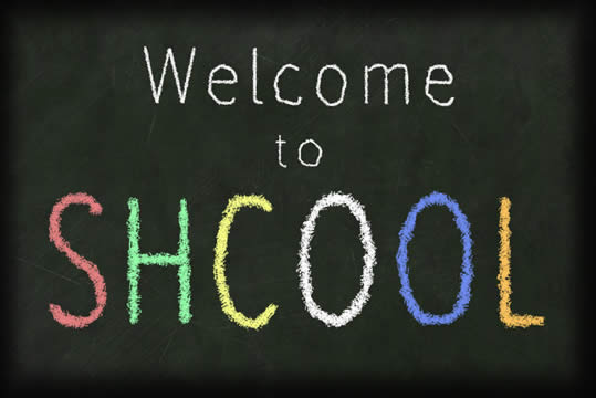 Message written on chalkboard: Welcome to School, with the word school misspelled