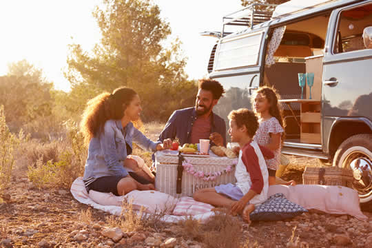 family on a picnic in nature alongside a camper