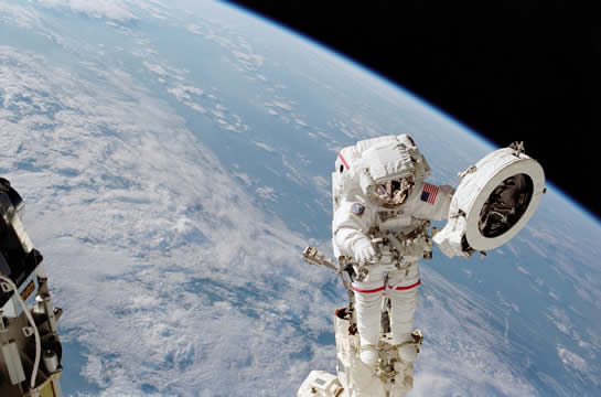 astronaut outside the International Space Station orbiting Earth