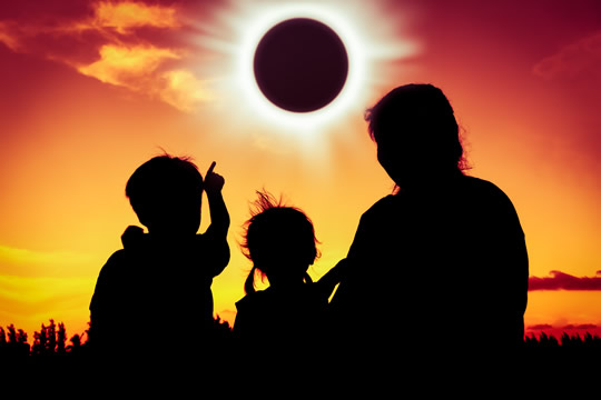 Silhouette of the backs of three family members looking at a solar eclipse
