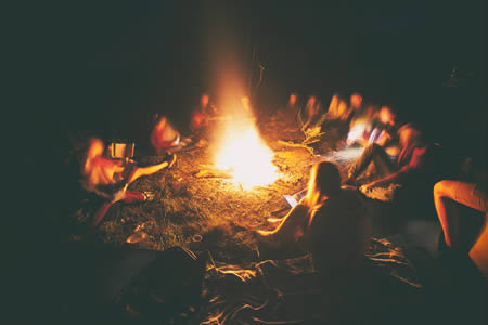 teens telling stories around a campfire