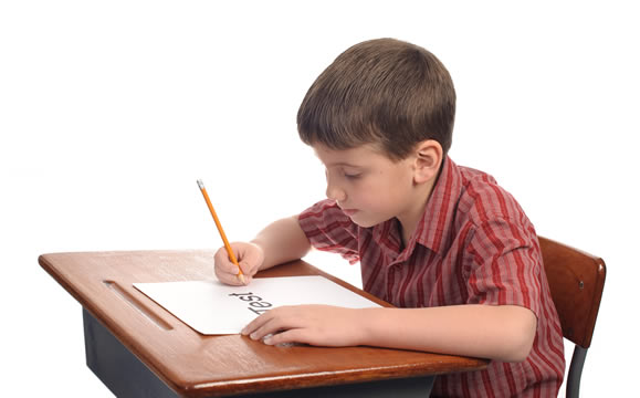 Boy taking test at classroom desk