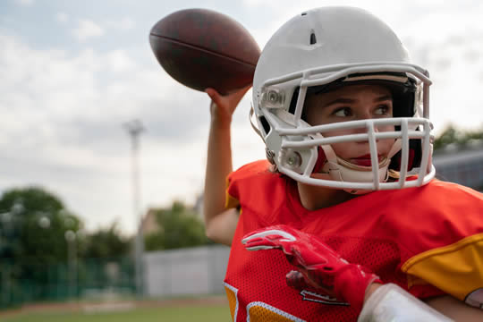 photograph of a girl in full football gear, getting ready to pass the ball