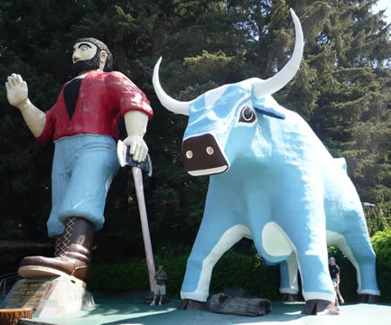 statue of a man in a red shirt and blue pants holding an axe, alongside a big blue bull