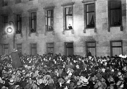 photograph of Hitler standing in a lit window of a building, crowds below in the street