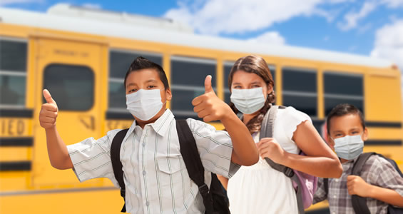 students wearing face masks in front of a school bus