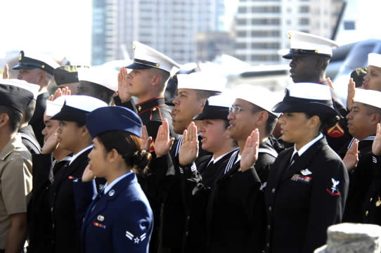 a groups of U.S. soldiers in uniform raise their right hands while taking the oath of allegiance