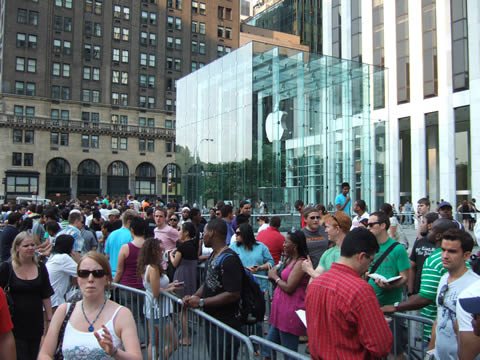 A crowd of people lined up in front of the glass-fronted cube of the Apple Store in Manhattan