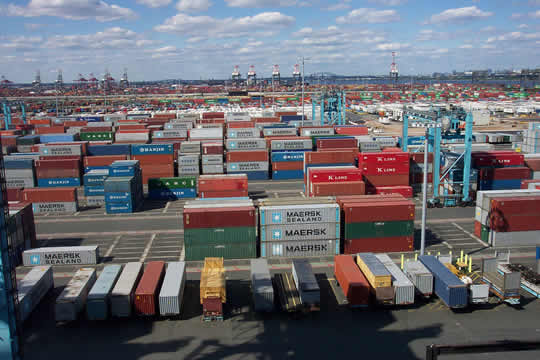 a port full of shipping containers with ships and a city visible in the background