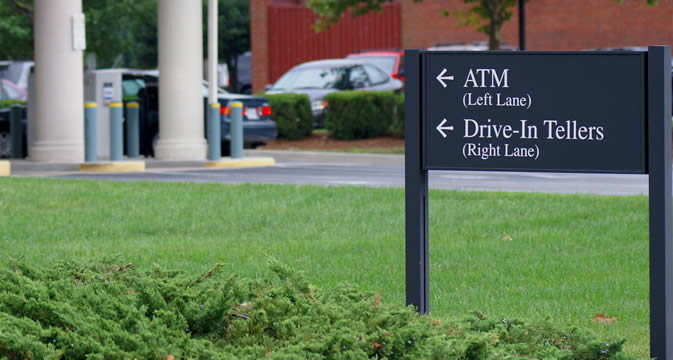 a sign showing the direction to a bank's drive-in tellers and ATM