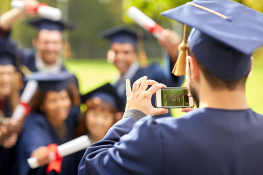 seniors in graduation caps and gowns taking photo with their diplomas