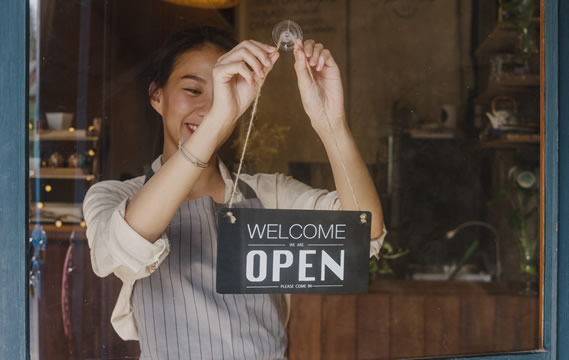 "woman hanging a ""Welcome, Open"" sign on a café door"