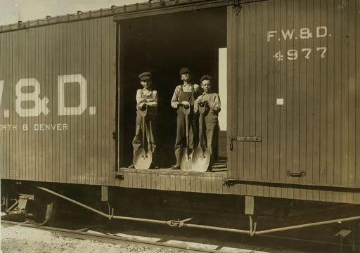 Photograph of three young boys standing in an open railroad car holding shovels