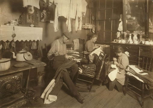 Photograph of a mother, father and daughter sewing by hand in a crowded tenement kitchen/living room