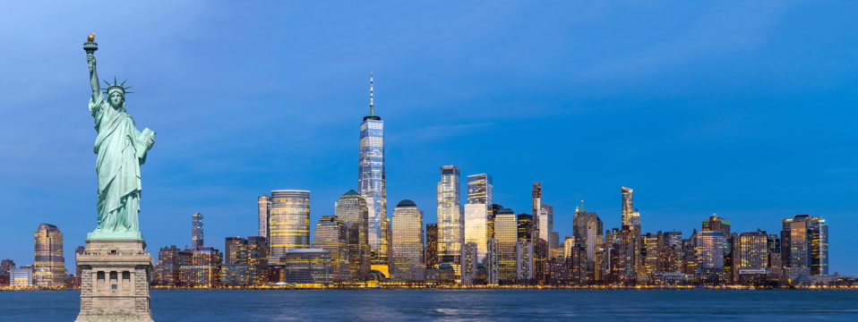 a panorama view of Lower Manhattan and the Statue of Liberty in New York Harbor