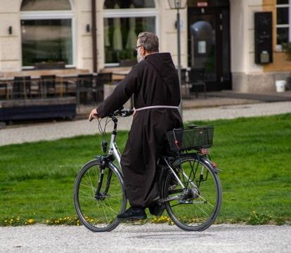 a friar riding a bicycle on a sidewalk