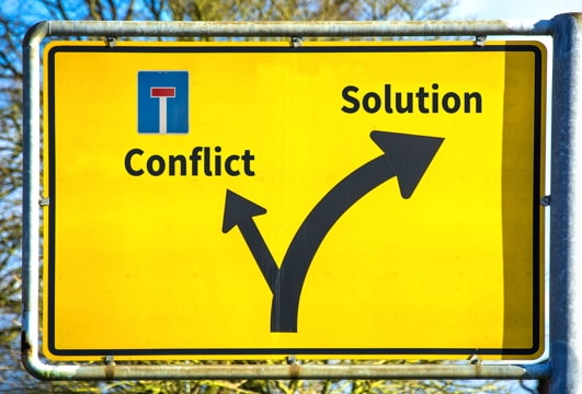 """road sign showing fork, one dead-end direction labeled """"conflict"""" and the other direction labeled """"solution"""""""