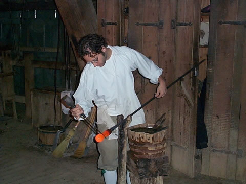 a colonist is working with red-hot glass in a colonial-style workshop