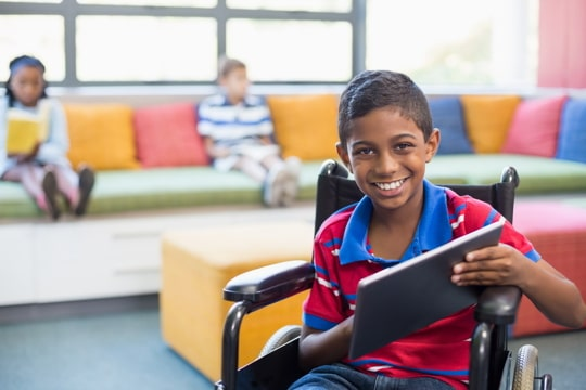 boy in wheelchair holding a tablet