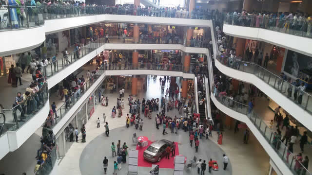 the open space of a mall with three floors of shops overlooking it