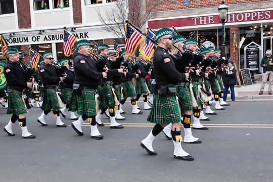 rows of bagpipe players dressed in green kilts and berets, carrying American flags