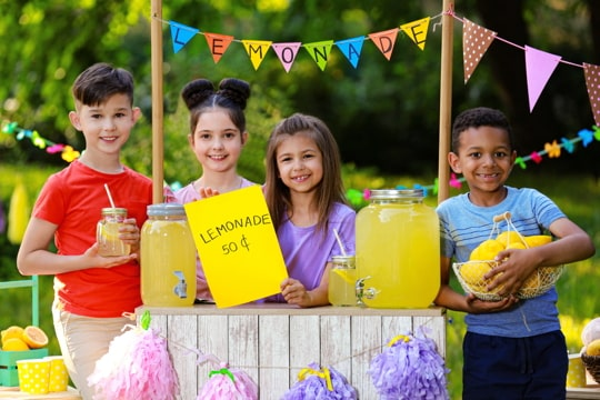 group of children selling lemonade at a lemonade stand