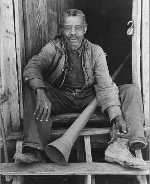 old photograph of a Black man sitting on a wooden step, holding a large horn