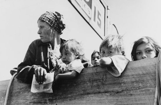 A mother and four children look sadly over the side of a pickup truck