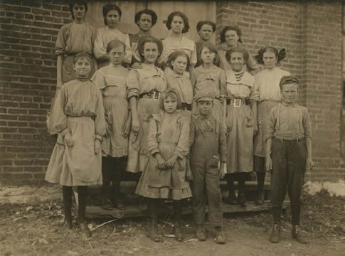 an old photograph of a group of children and young adults standing in front of a brick building