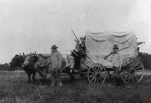 photograph of a covered wagon pulled by oxen; two women sitting on wagon, two men walking alongside it